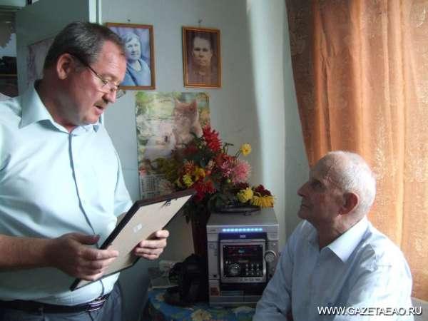 Поздравили юбиляра - Первый заместитель главы Ленинского сельского поселения Виктор Князев вручает юбиляру приветственный адрес.